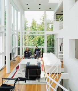 The current homeowners, Michael McCarthy and Marcia Myers, pictured at home in the Douglas Residence, spent years rehabilitating the structure. The double-height living room features a custom sofa and low table of Meier's design, and an Edward Fields rug based on a sketch Le Corbusier created in 1956 for a Tokyo theater.