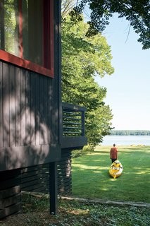 The cottage sits on an acre of mature trees, with a sloping lawn stretching to the pebbly shore of the inland lake. The Campbells regularly drag their kayaks down to the water's edge and set off toward the deeper waters of Lake Michigan.