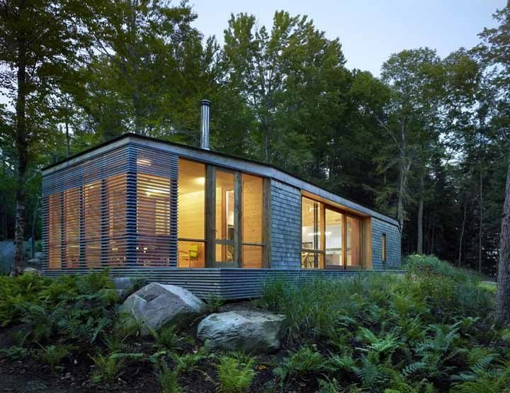 Exterior, Cabin Building Type, House Building Type, and Wood Siding Material Sited on a lake near Bracebridge, Ontario, this small-footprint family cottage was designed by Toronto firm superkül to integrate with its natural surroundings and minimize its environmental impact. The clients, a married couple, had mixed feelings about going completely modern with their cabin's aesthetic, so the architects created a sculptural wood form to bridge the gap between traditional and contemporary. Photo by Shai Gil.  Photo 47 of 101 in 101 Best Modern Cabins