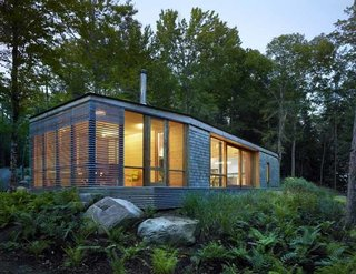 Sited on a lake near Bracebridge, Ontario, this small-footprint family cottage was designed by Toronto firm superkül to integrate with its natural surroundings and minimize its environmental impact. The clients, a married couple, had mixed feelings about going completely modern with their cabin's aesthetic, so the architects created a sculptural wood form to bridge the gap between traditional and contemporary. Photo by Shai Gil.