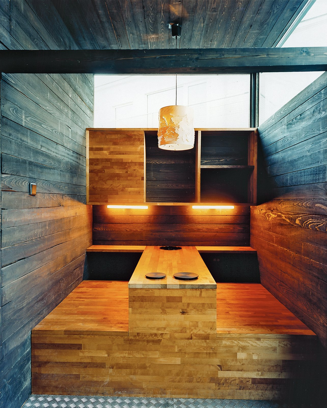 The kitchen table, built into the structure of the house, includes two hot plates. Rintala says these were inspired by the Korean way of cooking: Residents and guests will cook their own food at the table.  Photo 1 of 5 in A Norwegian Boxhome Gleams with Optimism