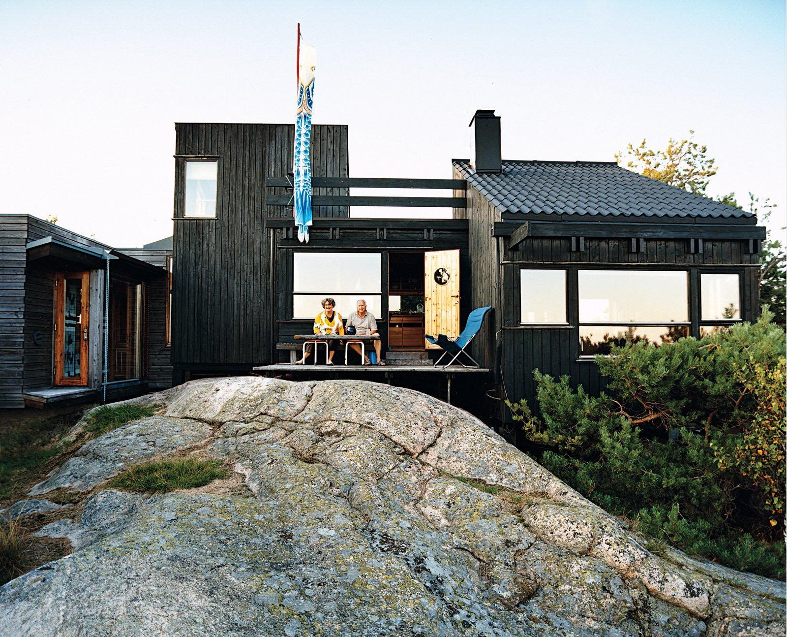 """Outdoor, Back Yard, and Small Patio, Porch, Deck """"People scold us if we don't raise the kite,"""" says Holm (sitting with Kiehl,). From the bench outside, the couple can wave to friends passing in boats and make use of the long summer evenings.  Photo 1 of 9 in Norwegian Wood"""