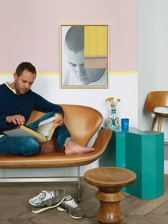 Aumas reads on a vintage Swan sofa by Arne Jacobsen. The teal side table is from a Berlin flea market; the walnut stool by Charles and Ray Eames is from an antique store in Brussels; Aumas himself made the art on the wall.