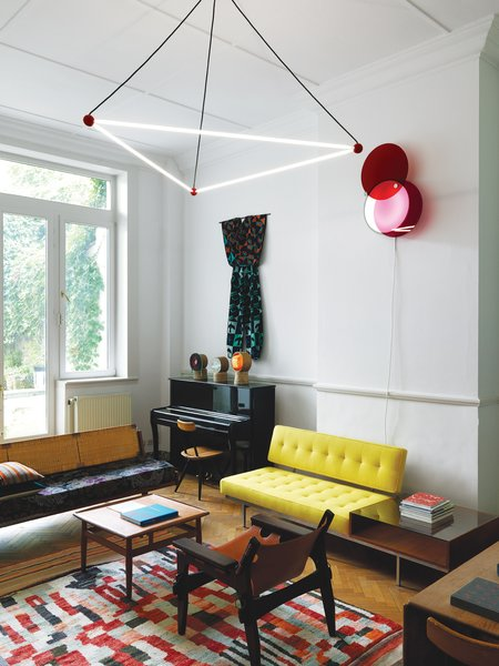 """Located just off the entry hall, this room opens onto a lush garden. The residents commissioned the overhead light from designers Sylvain Willenz and Hubert Verstraeten. """"The use of red billiard ball references Charles and Ray Eames's Hang-It-All coat rack,"""" says Smith. The wall-hung light is by the contemporary São Paulo–based designers Luciana Martins and Gerson de Oliveira. The rug is a Moroccan patchwork from the 1960s; the teak-and-leather Kilin chair is by Sergio Rodrigues; and the cane-backed sofa is a student daybed designed by Hans Wegner for Getama in the 1950s.  Photo 10 of 18 in A Neoclassical Gallery Home in Belgium"""
