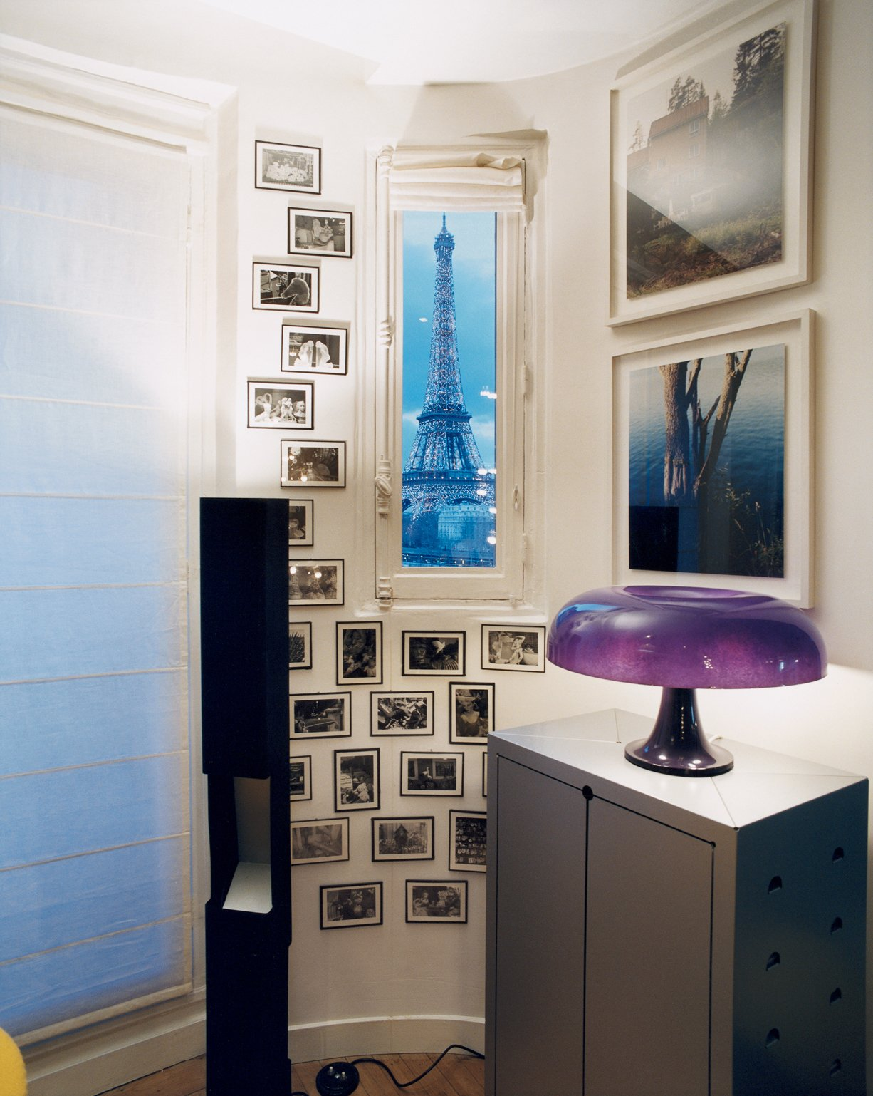 A Torbjorn Rodland photograph is flanked by Elysées sconces by Pierre Paulin. A lighted Bouroullec vase sits atop a vintage Raymond Loewy storage unit.  Photo 4 of 7 in 5 Modern Apartments in Paris from Like a Kid in a Candy Store