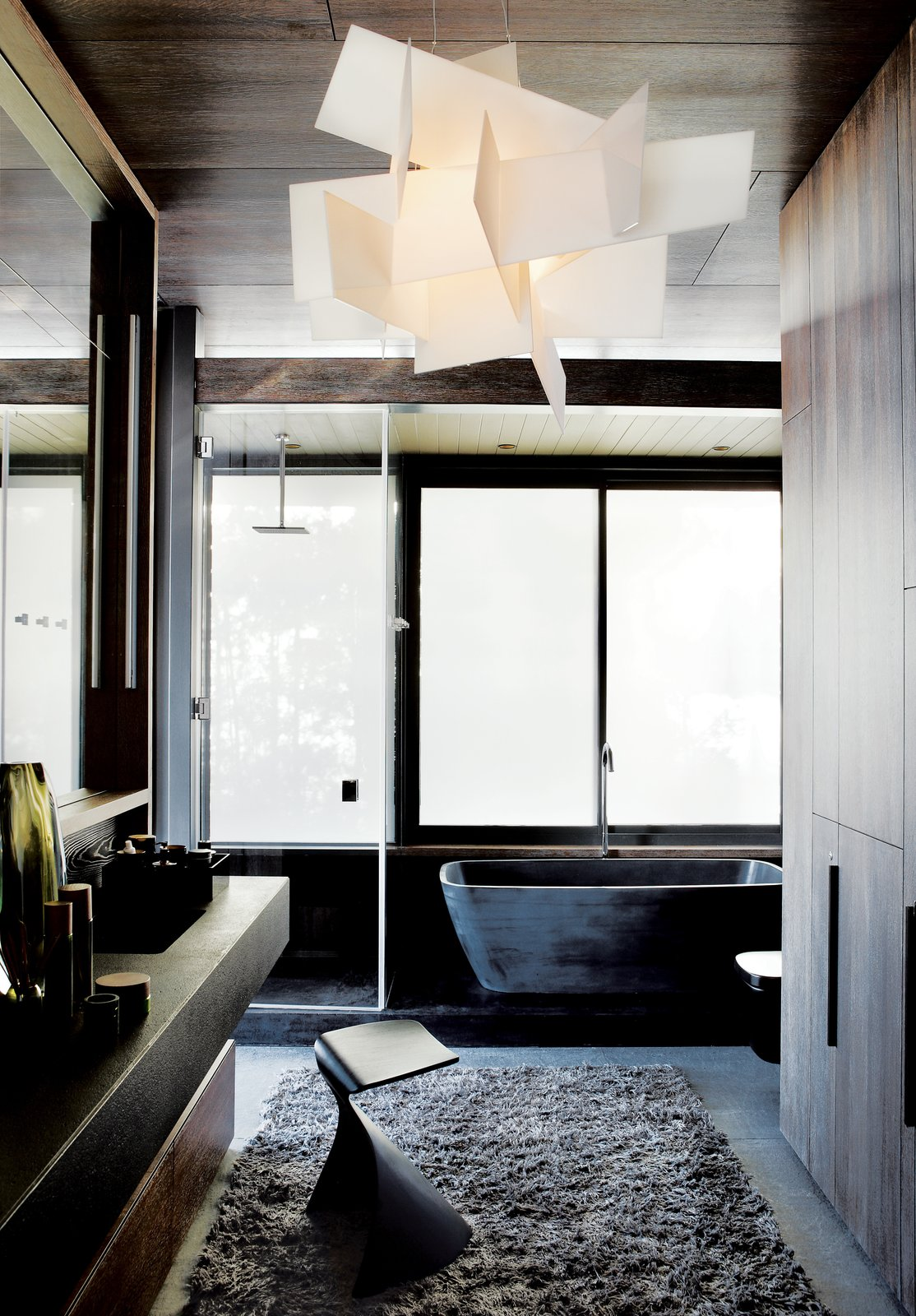 Bath Room, Concrete Floor, and Freestanding Tub In the master bath, sandblasted windows let in light while retaining privacy. The tub is from Dado, the vanity and stool are from Ligne Roset, and the Big Bang light is from Foscarini.  Photo 5 of 6 in A Sophisticated Penthouse in Cape Town