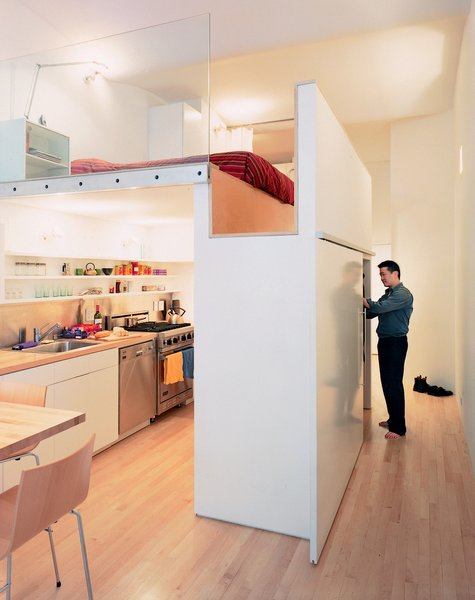 Raising the bed above floor level, architect Kyu Sung Woo converted this tiny studio into an open and comfortable home for Wonbo Woo. Photos by: Adam Friedberg Tagged: Storage Room, Closet Storage Type, and Under Stairs Storage Type.  Tiny Apartments in New York City by Allie Weiss from Tiny Kitchens We Love