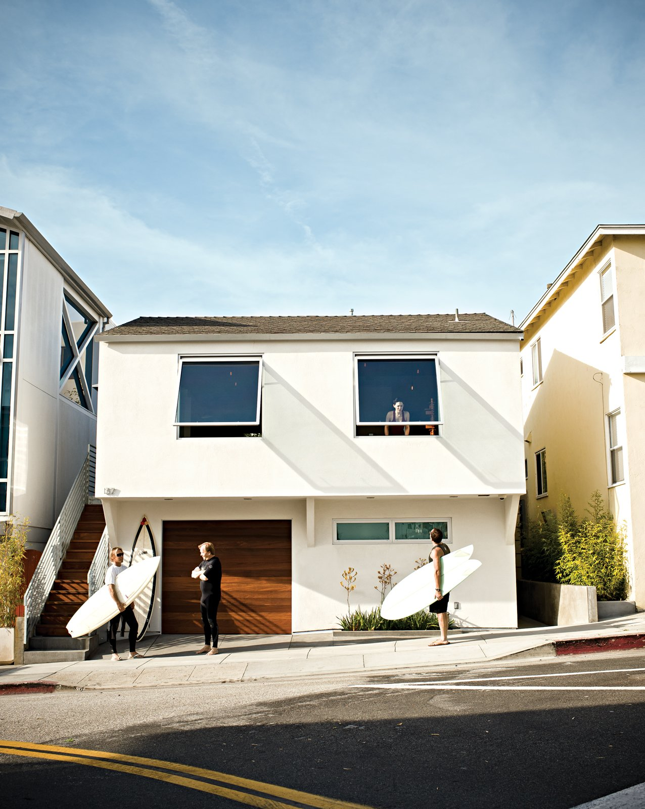 Joined by architect Michael Lee and friend Gus McConnell, Jacobson shouts up to Dukes that they're headed out for an impromptu surf session. Tagged: Exterior, Stucco Siding Material, and House.  Photo 2 of 18 in Less is More in this Manhattan Beach Bungalow