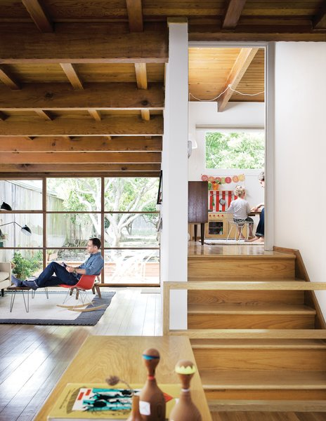The exposed wooden rafters and grid of windows in the living room are original to the house.