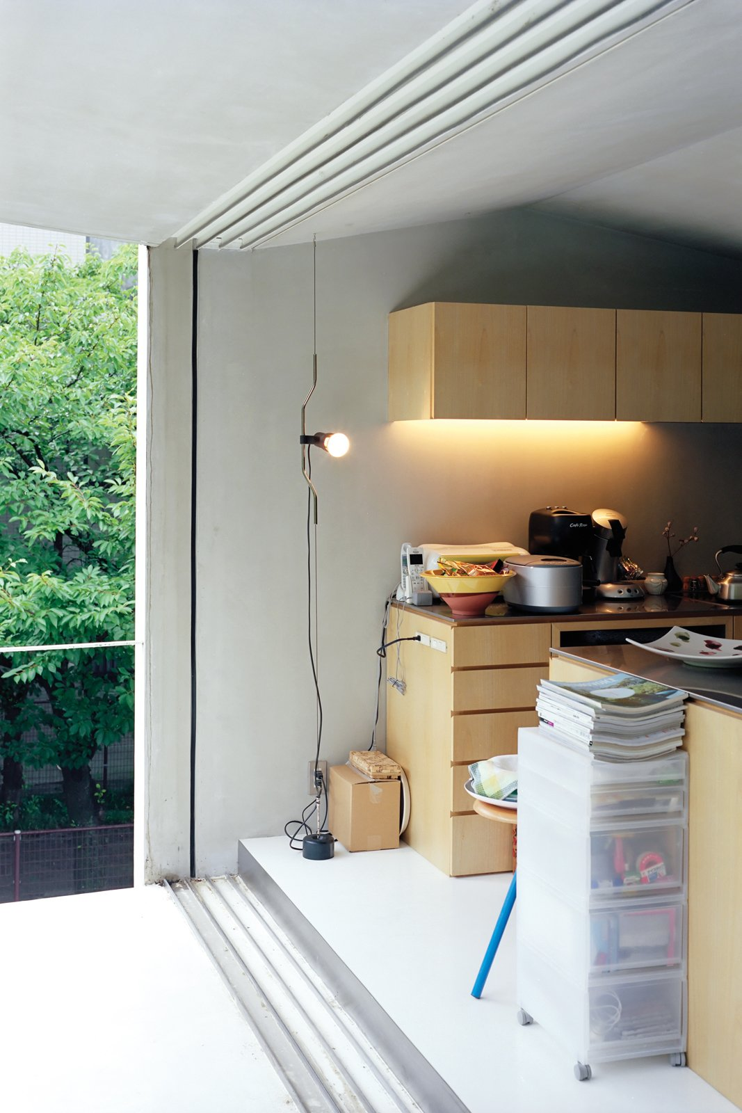 Custom-made paulownia cabinets and a roomy balcony keep the compact second-floor living-dining-kitchen area from feeling cramped or cluttered.  Photo 7 of 11 in Small Space Live/Work Box Home in Japan