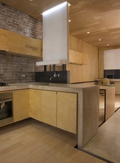 """The apartment, measuring just over 400 square feet, opens into the kitchen, which architectural designer Alan Y. L. Chan outfitted with a Dornbracht faucet and a sink of his own design. The black steel backsplash doubles as the back of a built-in bench on the other side. A concrete """"ribbon"""" serves as the main design concept and the countertop, and continues throughout the apartment. A built-in LG refrigerator is located just across the concrete floor at right. Image courtesy Brian Riley."""