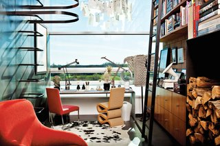 A silo ladder in the study leads to the roof deck. Both desk lamps are Tizios by Richard Sapper for Artemide; the pendant is a Zettle'z by Ingo Maurer; and the Kalos armchair and Solo desk chair are by Antonio Citterio for B&B Italia.