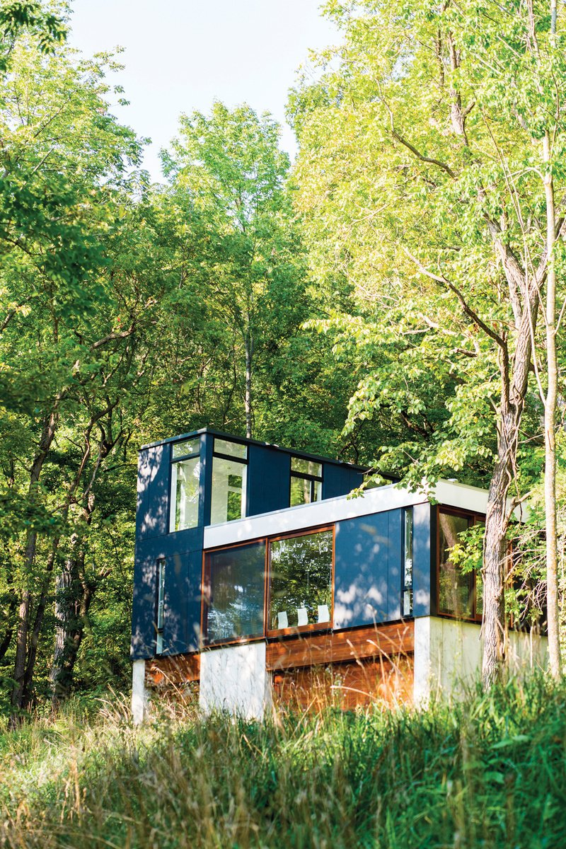 Exterior, Cabin Building Type, Flat RoofLine, and Glass Siding Material Set in the lush Wisconsin forest, this neatly stacked cabin was built vertically in order to minimize the amount of grading and landscaping necessary for construction. Photo by: Narayan Mahon  Photo 6 of 101 in 101 Best Modern Cabins from Striking Designs in Wisconsin