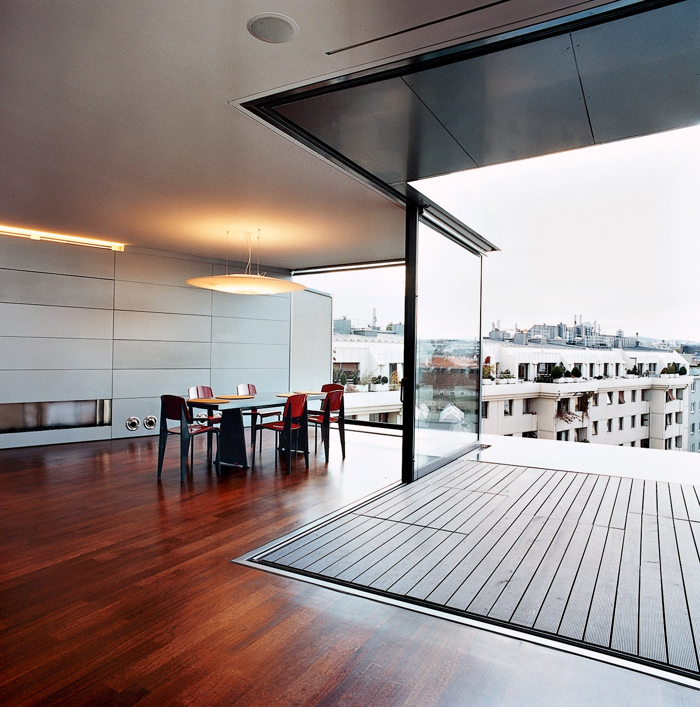 In Vienna, a dazzling penthouse by Delugan Meissl has boldly inserted itself between traditional rooftops of the city's Wieden district like a recently landed alien intruder. The engineering of House Ray 1's load-bearing structure was extremely complex. Since the house had to be built on top of an old building, the architects opted for lightweight steel skeleton construction. The living/dining area has sliding glass walls that open to the back terrace and pool.  Photo 4 of 16 in The Penthouse Has Landed