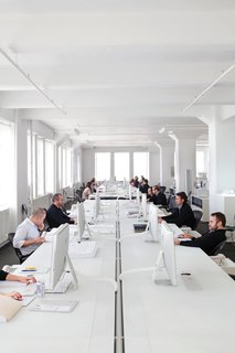 All Phifer's 25 employees work around a hundred-foot table. Phifer maintains the monochromatic palette down to the mouse pads.