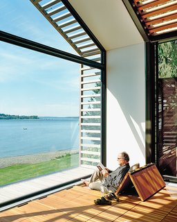 The Trues host parties in the glass-walled structure, located steps from their vacation home, or they escape to it to catch some rays and read a book. Bill reclines on cushions hidden under the reclaimed-fir floorboards that are propped up with Sugatsune hinges.