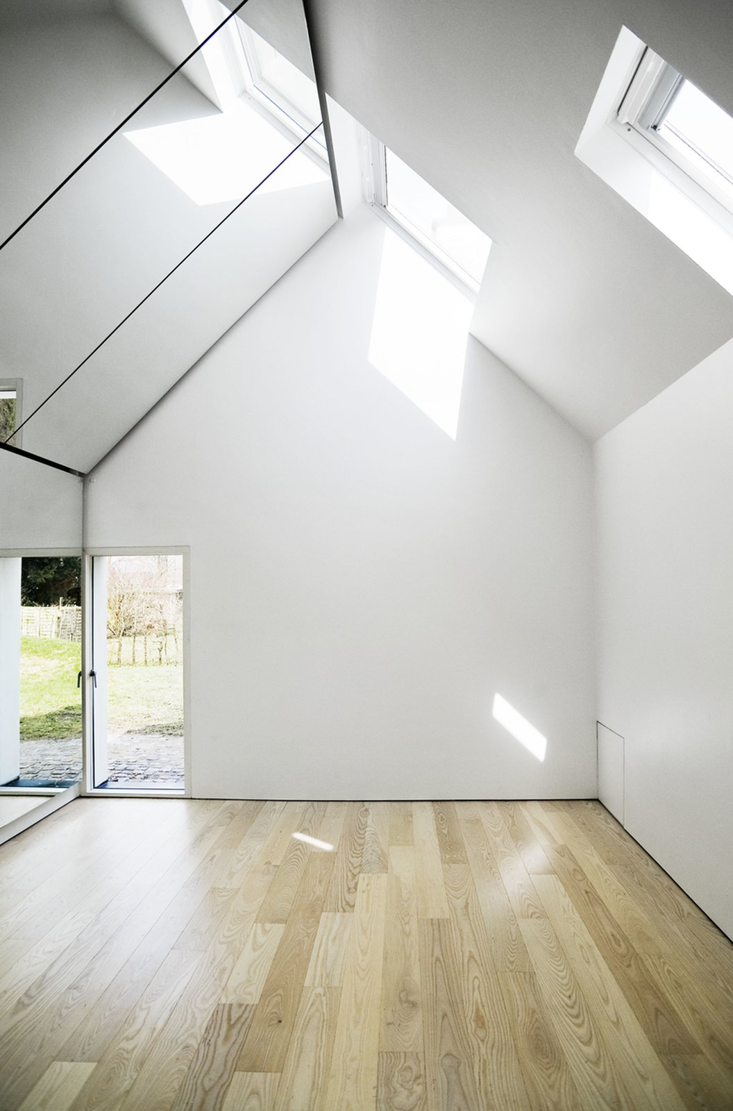 """Inside the studio lies a spacious, light-filled interior. It is the perfect place for Søren's comedy shows, sketches, and music, but also provides a calm, pleasant space shared by the whole family. """"Our kids enjoy being in there and playing or falling asleep on the floor as well,"""" says Lone.  Photo 6 of 6 in Danish Farmhouse Turned Contemporary Art Studio"""