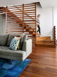 In the George Street Residence, architect Julie Fisher designed a custom walnut staircase. She selected a Honeycomb rug from One King's Lane and a Bensen Edward sofa from ID Chicago to outfit the living room.