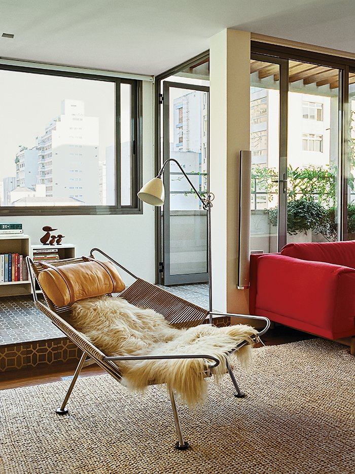 """Living Room, Chair, Shelves, Floor Lighting, and Sofa A Flag Halyard chair by Hans Wegner in long-haired sheepskin occupies one end of the living room.  Photo 2 of 11 in 10 Ways to Bring a Little """"Hygge"""" Into Your Home from Amazing Garden Oasis in São Paulo Born from a Five-Year Search and Renovation"""