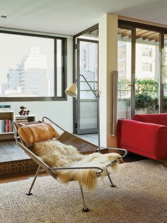 A Flag Halyard chair by Hans Wegner in long-haired sheepskin occupies one end of this living room.