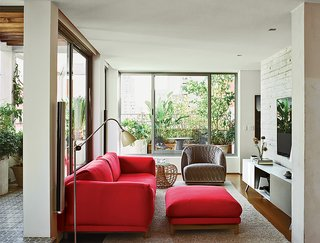 Amazing Garden Oasis in São Paulo Born from a Five-Year Search and Renovation - Photo 6 of 15 - The living room is furnished with a cherry-red Rest sofa and ottoman by Muuto, a Nest footstool by Foersom & Hjort-Lorenzen for Cane-Line, and a Redondo armchair by Patricia Urquiola for Moroso. A Kast modular storage unit by Maarten Van Severen for Vitra sits under the television.
