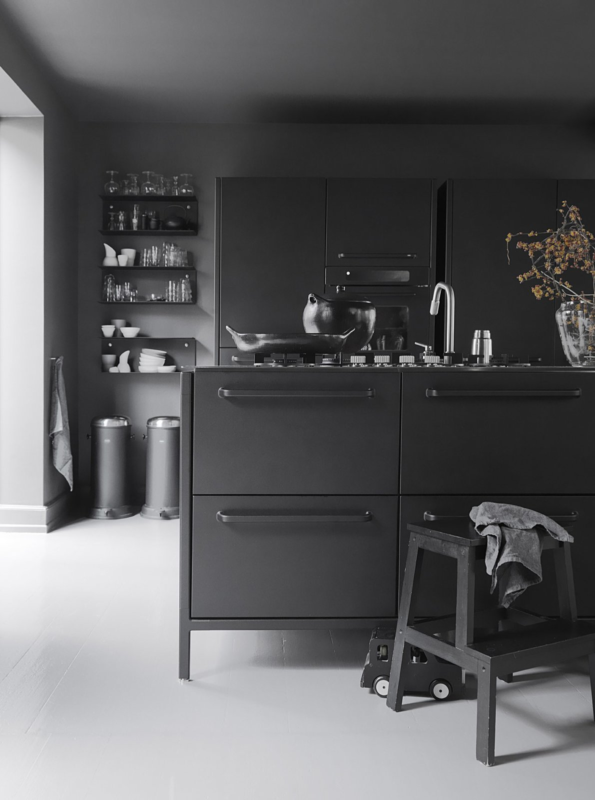 Kitchen and Painted Wood Floor The iconic waste bin that gave Vipp its start is a mainstay in the Egelunds' home, as are many of the company's streamlined design solutions. The waste bins, shelves, glasses, and ceramics are by Vipp.  Photo 6 of 11 in 10 Stunning Ways to Use Black in Your Kitchen from Black, White, and Gray All Over: Monochromatic Copenhagen Townhouse