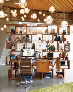This multifunctional shelving unit designed by Omer Arbel works well for an avid record collector, who uses the unit's many shelves to host a variety of objects, ranging from plants to speakers and vinyls. The desk component follows the same geometric logic as the rest of the piece, and the regular angles of the unit are in contrast to the home's unusual angular shape.
