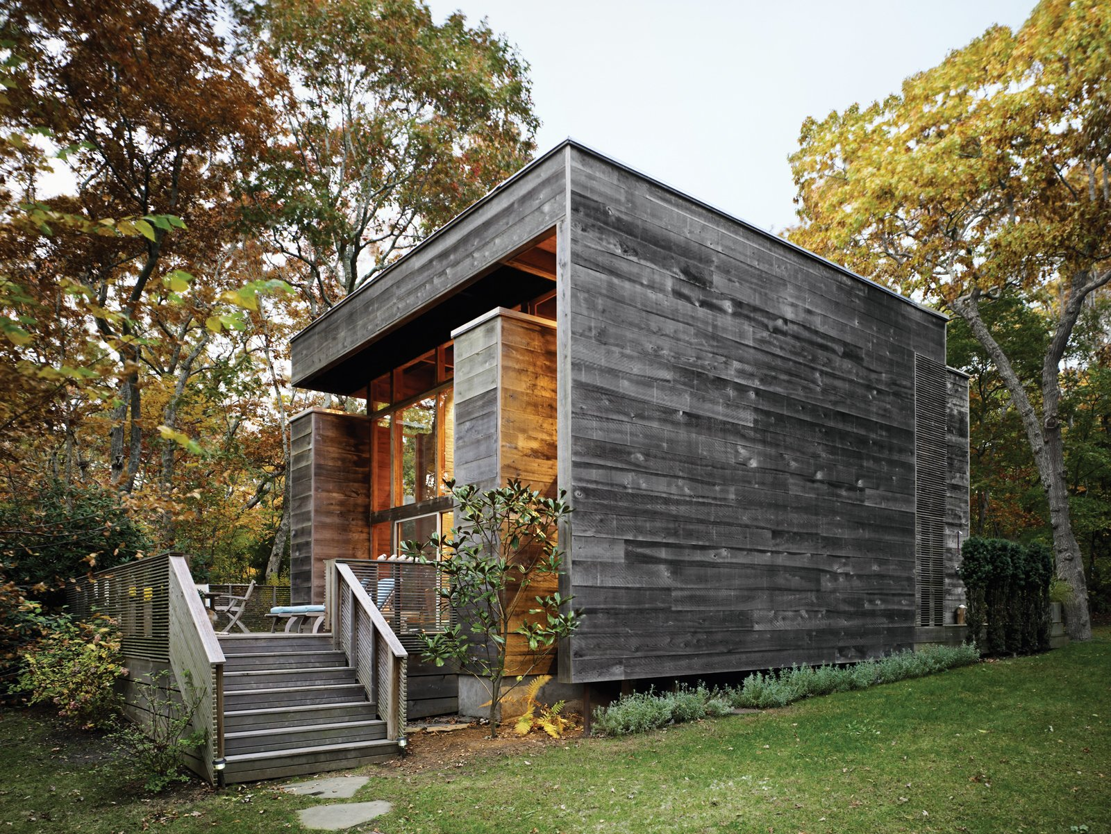 Exterior, House Building Type, Cabin Building Type, Wood Siding Material, and Flat RoofLine Bates Masi's renovation and expansion of Harry Bates's 1967 house in Amagansett, New York, salvaged much of the home's original cypress decking and incorporated subtle additions to the exterior. Because cypress quickly develops a patina, it was only a matter of weeks before the new facade matched the color of the original wood siding. Photo by Raimund Koch.  Photo 1 of 17 in Long Island Summer Home Gets a Modern Addition