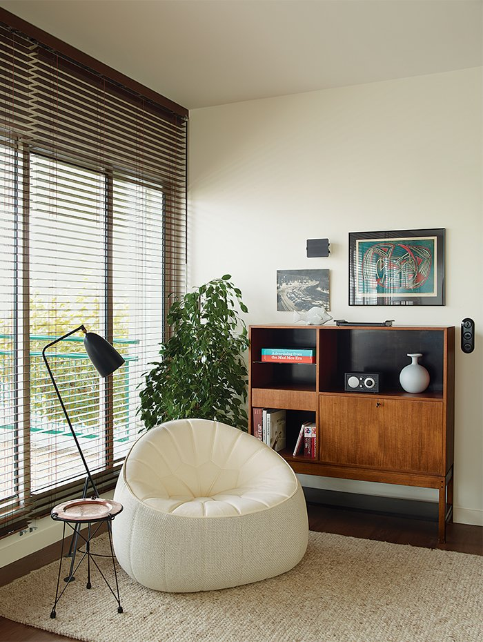 A Noé Duchaufour-Lawrance chair, Charlotte Perriand wall sconce, and Greta Grossman Grasshopper floor lamp round out a corner in the living room. Deau made the side table herself.  Photo 11 of 17 in Modern Home Furnished With Flea Market Finds