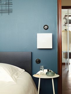 Modern Home Furnished With Flea Market Finds - Photo 6 of 17 - Farrow & Ball's Hague Blue covers a wall in another bedroom. The light switches here, and throughout the apartment, are Hager's 1930 series. Deau stationed a 1970s-era sconce next to the bed.