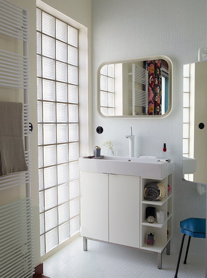 Bath Room and Drop In Sink The Basics series radiator by Italian manufacturer Tubes doubles as a towel rack in the bathroom. Deau purchased the cabinet and mirror from Ikea and she found the stool at a flea market.  Photo 4 of 17 in Modern Home Furnished With Flea Market Finds