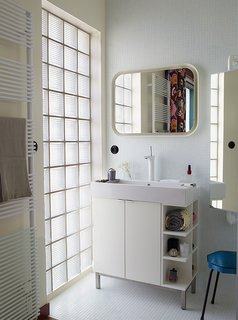 The Basics series radiator by Italian manufacturer Tubes doubles as a towel rack in the bathroom. Deau purchased the cabinet and mirror from Ikea and she found the stool at a flea market.