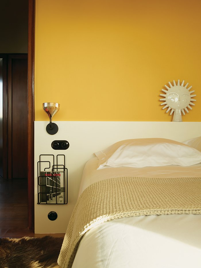 Bedroom, Bed, and Wall Lighting Farrow & Ball's Babouche yellow enlivens one of the bedrooms.  Photo 5 of 17 in Modern Home Furnished With Flea Market Finds