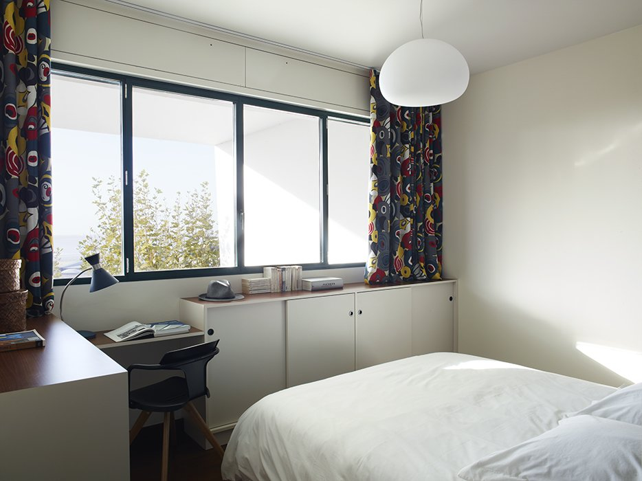 Bedroom, Bed, Ceiling Lighting, Table Lighting, Pendant Lighting, and Chair The curtains are made from graphic Gastón y Daniela fabrics.  Photo 8 of 17 in Modern Home Furnished With Flea Market Finds
