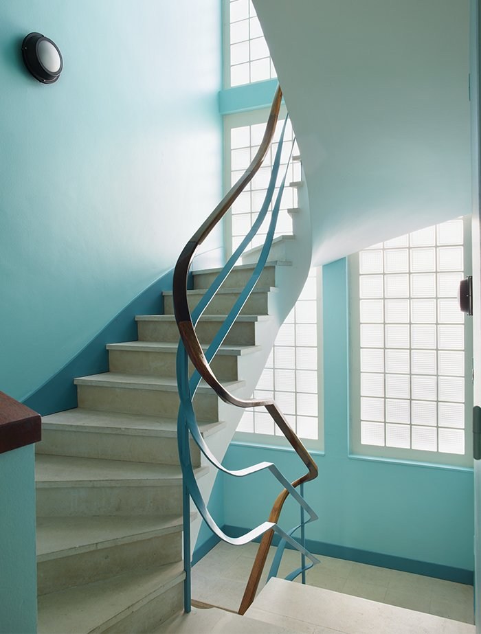 Staircase, Metal Tread, and Wood Railing The apartment can be reached by a winding staircase.  Photo 10 of 17 in Modern Home Furnished With Flea Market Finds