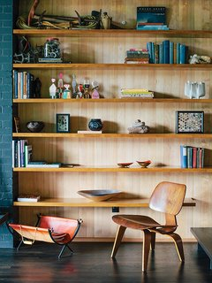 A vintage Molded Plywood Lounge Chair (LCW) by Charles and Ray Eames for Herman Miller sits in front of built-in shelving in untreated hemlock.