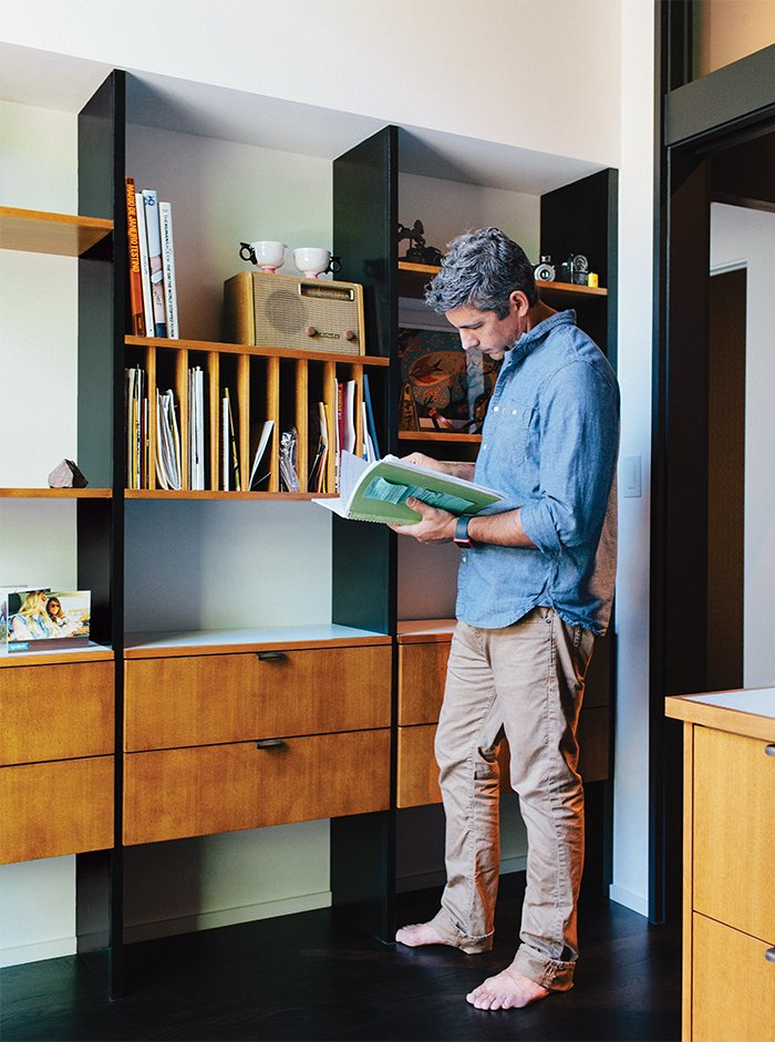 Office, Study Room Type, Library Room Type, and Shelves Resident Ty Milford peruses a book by the George Nelson–inspired built-ins fabricated by Big Branch Woodworking  Photo 8 of 19 in Midcentury Renovation in Portland Capitalizes on Nature with Seven Doors to the Outside