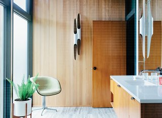The flooring in the master bath is vein-cut Ocean Silver travertine. The custom bathroom vanity is stained birch, the polished chrome fixtures are from Hansgrohe's Axor Uno2 line, and the chair is upholstered in Checker by Alexander Girard for Maharam.