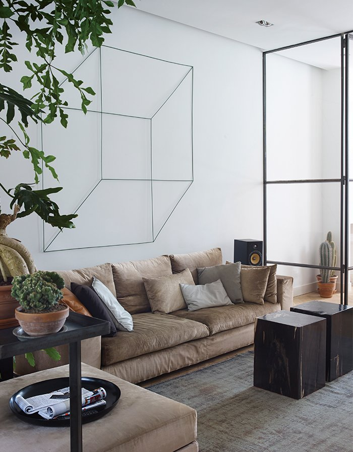 In the main living area of Frank Nederhof's renovated Amsterdam flat, a geometric sculpture by Antonino Sciortino hangs above an Erik Kuster sofa. The coffee tables are made from fossilized wood so heavy that each one requires two people to lift it.  Photo 1 of 6 in A Restless Real Estate Developer Builds His Ideal Live-Work Space