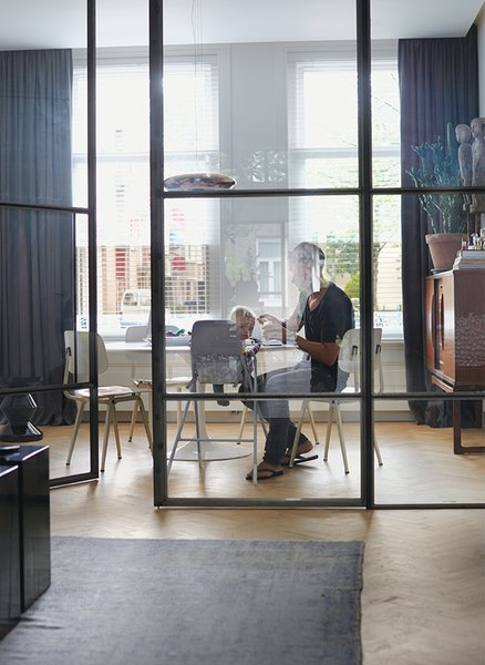 Nederhof and his son Scott sit at a Tulip table by Eero Saarinen for Knoll in the flexible office area. The chairs are by Friso Kramer for Ahrend, and the Corona pendant light is from Established & Sons.