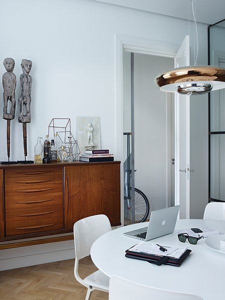 Nederhof purchased the vintage teak dresser from an online secondhand store. On it stand fertility statues and a miniature sculpture by Antonino Sciortino. The steel-framed glass doors fold back into the wall, and the space is oriented so clients can enter the office without traipsing through the entire flat.