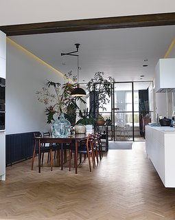 The living room, dining room, and kitchen are arranged in a 60-foot-long enfilade. The pendant light above the table is Nemo by Franco Albini for Cassina. A grouping of succulents and Monstera deliciosa plants act as a natural room divider.