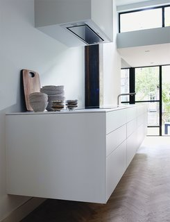 The sleek, white kitchen is by Bulthaup.