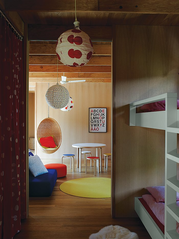 Kids Room, Playroom Room Type, Lamps, and Bedroom Room Type The couple's ten-year-old twins have connecting rooms next to a play space furnished with Aalto stools, a table from Artek, and a Nanna Ditzel rattan hanging chair purchased at Interstudio.  Photo 7 of 9 in Local Wood Clads Every Surface of This Idyllic Australian Getaway