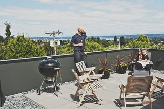 Rex folding rocker chairs from Design Within Reach are paired with black galvanized-steel planters from Ikea on the building's roof deck.