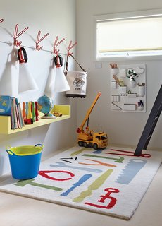 The boys' playroom is outfitted with a Uten.Silo wall organizer by Dorothee Becker for Vitra and a pair of May Day lamps by Konstantin Grcic for Flos that dangle from a set of Peace hooks by Louise Hederström for Maze.