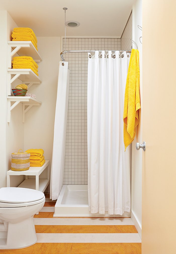 Bath Room, Corner Shower, One Piece Toilet, and Ceiling Lighting In the guest bathroom, a set of Senegalese nesting baskets mirrors the yellow-and-white pattern on the linoleum floor.  Photo 14 of 25 in 25 Bold Ways to Decorate with Yellow from Smart Interior Update Shows When a Gut Renovation Isn't Necessary