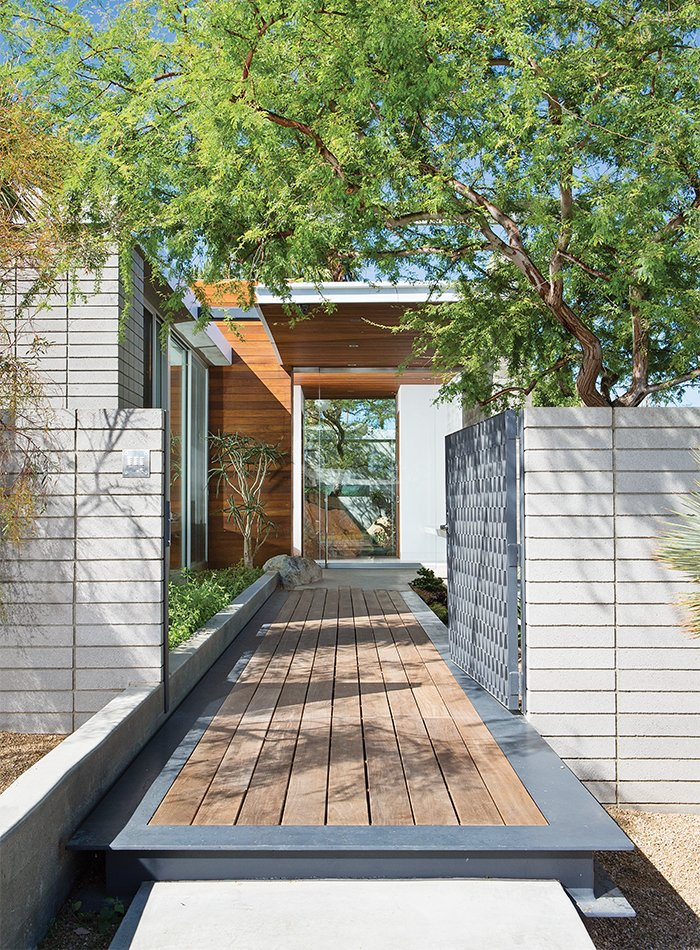An ipe walkway leads past a steel gate to the guesthouse. Tagged: Exterior, House, and Wood Siding Material.  Photo 2 of 12 in Vacation Home in the California Desert is a Modernist Oasis