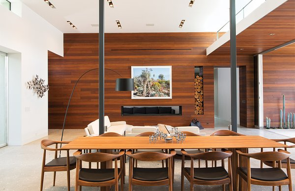 Ipe paneling and concrete floors continue into the living area, where a photograph by Scott McFarland hangs above the fireplace. Surrounding the dining table, by Riva 1920, are walnut chairs the couple found locally.