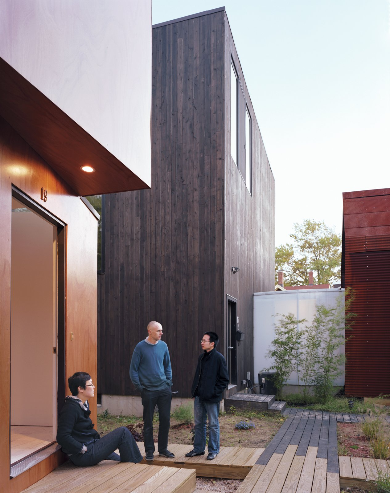 Schenk, Kim, and Kaewlai chat outside of X-Small, standing on the reclaimed wood used to build the boardwalks that connect all four properties. The translucent corridor connecting Small and Medium illuminates the common space throughout the evening.  Photo 8 of 11 in Four Houses and a Future